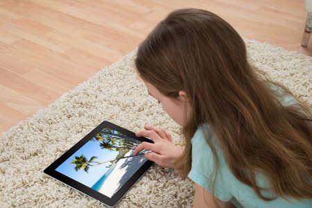 デジタル タブレットの写真を見てカーペットの上に横たわる少女