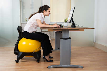 woman posture: Businesswoman Bending In Front Of Computer While Sitting On Fitness Ball In Office