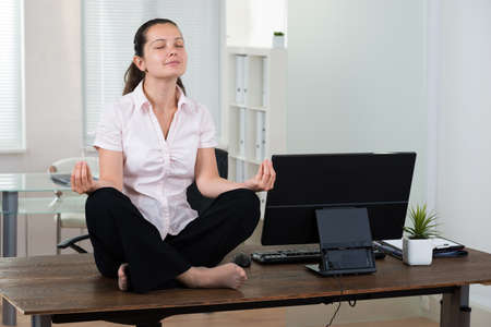 meditating: Young Businesswoman Doing Meditation On Desk In Office Stock Photo