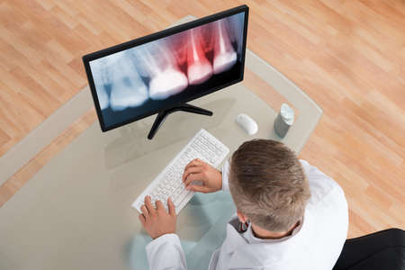 Young Male Dentist Looking At Teeth X-ray On Computer