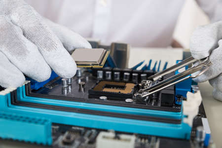 hardware repair: Close-up Of Person Hands Installing Central Processor In Motherboard Stock Photo