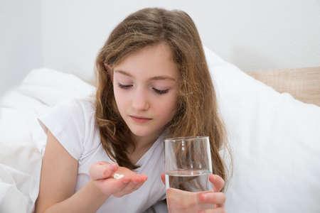 pastillas: Chica en la cama que toma la p�ldora con vaso de agua en el dormitorio