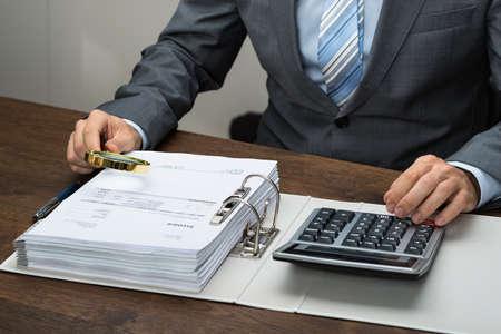 impuestos: Primer plano de hombre de negocios Inspección de Recibos Con La Lupa En La Oficina