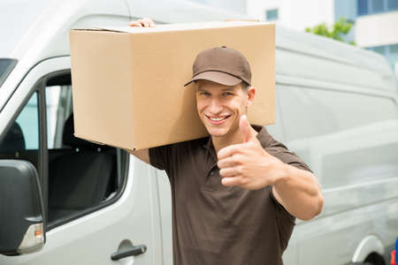 deliveryman: Happy Delivery Man Carrying Cardboard Boxes Showing Thumbs up Sign