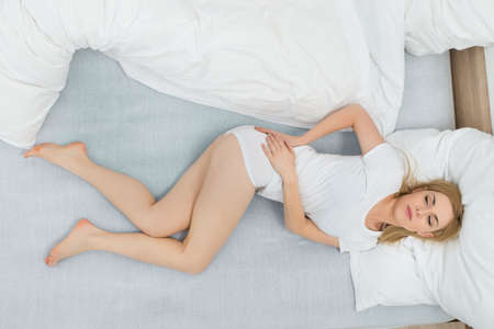 High Angle View Of Young Woman In Bed Having Back Pain Stock Photo