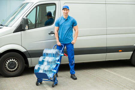 standing water: Young Happy Delivery Man Holding Trolley With Water Bottles Stock Photo