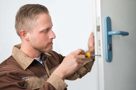 lock: Portrait Young Male Carpenter Repairing Door Lock