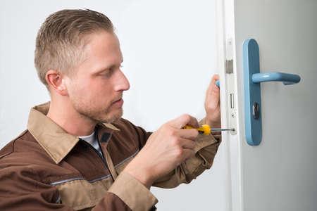 carpintero: Retrato masculino joven carpintero Reparación bloqueo de la puerta Foto de archivo