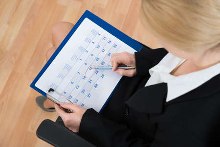 event planner: Close-up Of Businesswoman Marking Date With Pen On Calendar