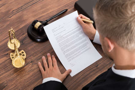derecho penal: Primer Del Juez Masculino Papel lectura en la sala de tribunal
