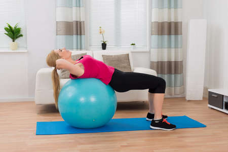 lying on stomach: Young Happy Woman Exercising With Fitness Ball Stock Photo