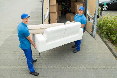 carga: Dos feliz Hombre Trabajadores Poner Muebles Y Cajas De Camión Foto de archivo