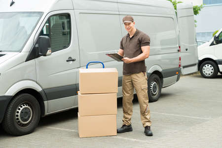 courier man: Young Happy Delivery Man With Cardboard Boxes Writing On Clipboard Stock Photo
