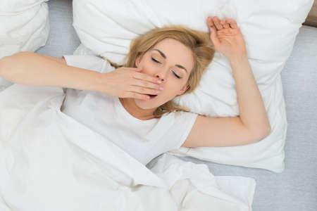 Mujer joven que bosteza en cama en el país Foto de archivo