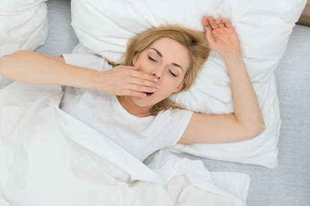 yawning: Young Woman Yawning In Bed At Home