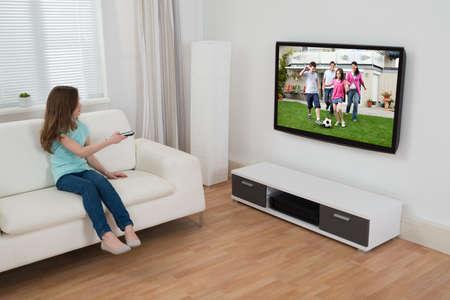 personas viendo television: Chica sentado en el sofá viendo la televisión en casa