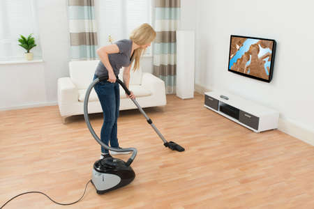 vacuum: Young Woman Cleaning Floor With Vacuum Cleaner At Home Stock Photo