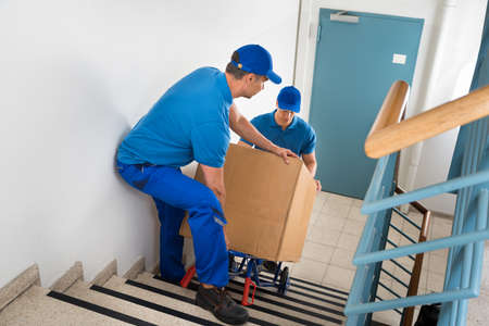 moving: Two Male Movers Walking Downward With Box On Staircase