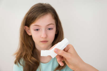 Close-up Of Person Hands Holding Inhaler In Front Of Girl