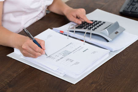 Accountant: Female Accountant Calculating Bills With Calculator In Office Stock Photo