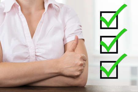 Close-up Of Businesswoman With Checklist Showing Thumb Up At Desk Archivio Fotografico