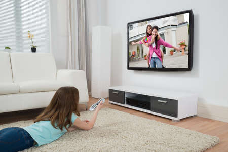 sofa television: Girl With Remote Control Watching Movie On Television In Living Room Stock Photo