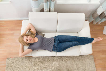 woman on couch: Young Beautiful Woman Sleeping On Sofa At Home