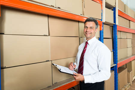 warehouse: Happy Manager Writing On Clipboard In Distribution Warehouse Stock Photo