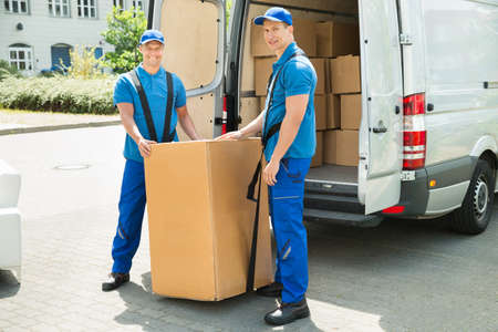 work load: Two Happy Movers In Blue Uniform Loading Boxes In Truck