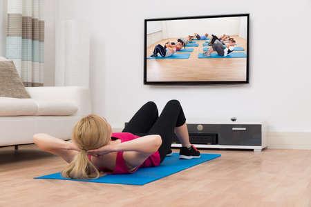 tv: Jeune femme exerçant sur le tapis bleu en regardant la télévision en Maison Banque d'images