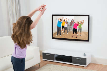 television: Girl Looking At Television While Doing Exercise At Home Stock Photo