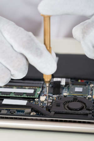 repairer: Close-up Of Person Hands In Glove Repairing Laptop Motherboard