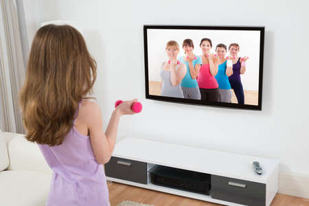 Fitness Girl Exercising With Dumbbell In Front Of Television At Home