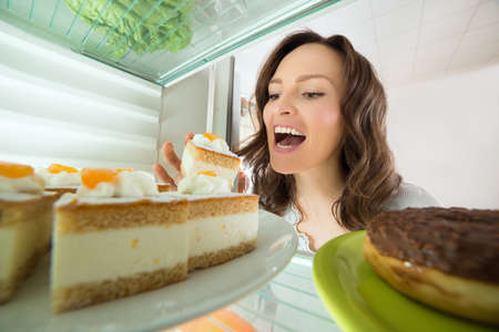 refrigerator with food: Hungry Young Woman Eating Slice Of Cake From Fridge At Home Stock Photo