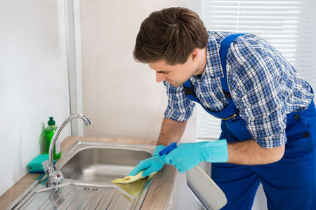 dirty house: Young Worker Wearing Glove Cleaning Steel Sink In Kitchen Room