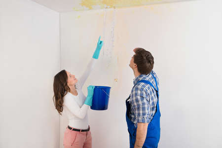 Young Woman With Bucket Showing Water Leaking From Damage Ceiling To Maintenance Guy Imagens - 43001457