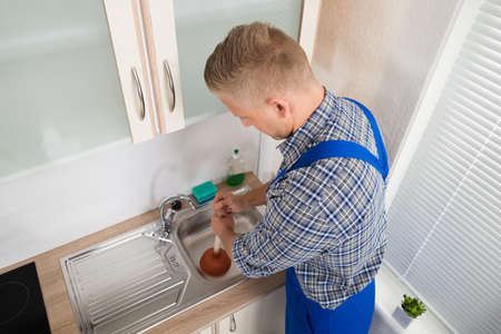 fontanero: Fontanero Hombre Usando émbolo en acero inoxidable fregadero en la cocina