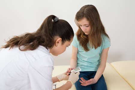 pacjent: Doktor W Labcoat pomiaru poziomu cukru we krwi Dziewczyna z Glukometr