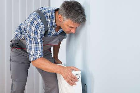 radiador: Retrato De Hombre fontanero fijación del radiador en la pared