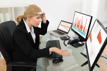 sales manager: Frustrated Businesswoman Looking At Graph On Computer At Desk In Office