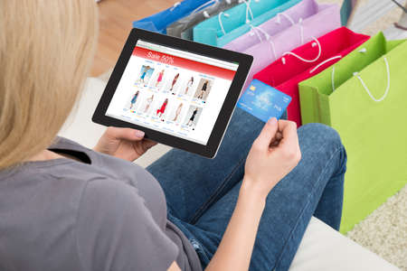 buying online: Close-up Of Young Woman Shopping Online On Digital Tablet With Credit Card