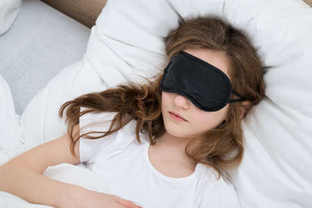 Girl Sleeping On Bed With Black Sleep Mask In Bedroom Stock Photo