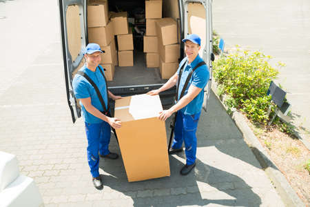 Two Happy Movers In Blue Uniform Loading Boxes In Truck