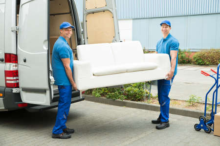 Two Happy Male Workers Putting Furniture And Boxes In Truck