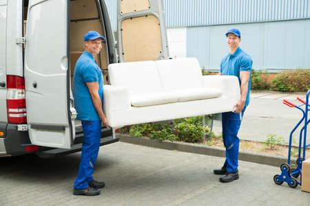 Twee Gelukkige mannelijke werknemers Putting Meubilair En Dozen In Truck