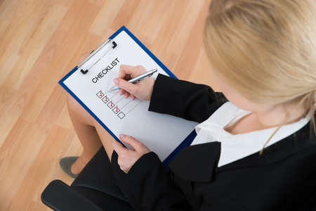 Businesswoman Marking Checklist With Pen On Clipboard At Workplace