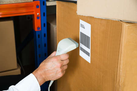 barcode scanner: Close-up Person Hands With Barcode Scanner Scanning Label On Box