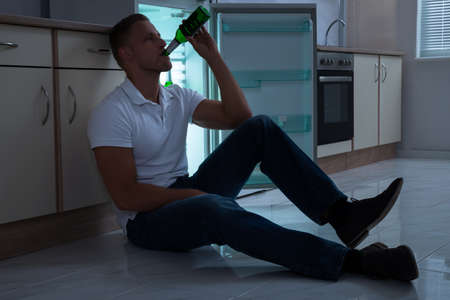 near beer: Young Man Sitting Near The Cabinet And Drinking Beer In Kitchen Stock Photo