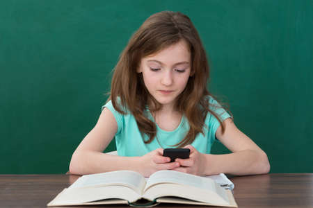 schooler: Girl Using Mobile Phone While Studying In Classroom