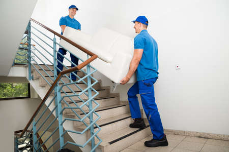 Two Happy Male Movers In Uniform Carrying White Sofa On Staircase 스톡 콘텐츠